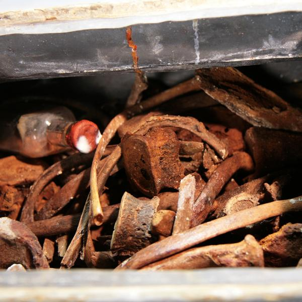 Detall de l'interior de l'urna. S'observen les restes òssies i l'ampolla conservats a l'interior (Autor: Marisol Cidrás)